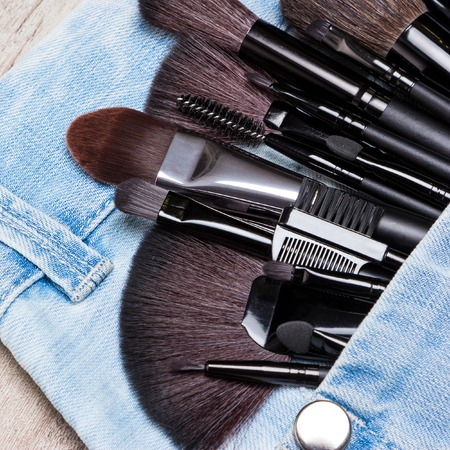 eyebrow trimming: Professional tools of make-up artist in blue jeans pocket. Sponge tip applicators and makeup brushes: for applying foundation, powder, blush, eyeshadow, eyebrow brushes and others. Selective focus