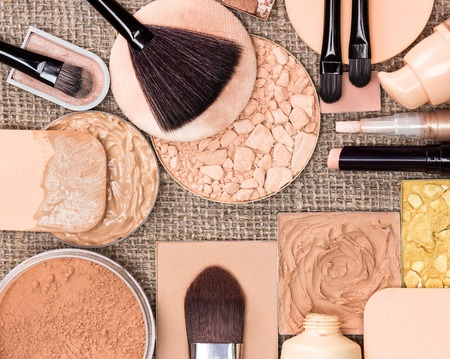 Makeup products to create the perfect complexion. Liquid and cream-to-powder foundation, concealers, compact, loose and shimmer golden powder, brushes and cosmetic sponges on sackcloth Фото со стока