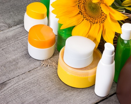 ecologically: Different body care cosmetics and sunflowers in wicker basket on old wooden planks. Set of ecologically clean skincare cosmetic products. Small copy space