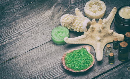 scrubbers: Spa and pampering products and accessories background. Sea salt in shell, body scrubbers, skin care cream, natural honey scrub, essential oils on old wooden planks. Copy space. Retro style processing