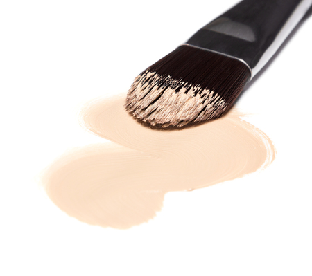 Close-up of flat makeup brush with sample of liquid foundation light shade on white background. Focus on the tip of brush