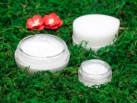 nourishing: Organic skin care products. Close-up of jars with moisturizing and nourishing creams surrounded by green moss. Natural cosmetics for women