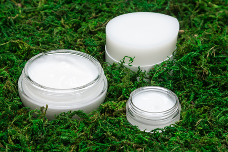 Organic skin care products. Close-up of jars with moisturizing and nourishing creams surrounded by green moss. Natural cosmetics for women