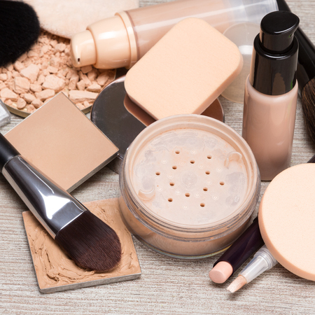 loose skin: Makeup products and accessories to even out skin tone and complexion. Concealers, bottles of liquid foundation, loose and compact powder, makeup brushes and cosmetic sponges on shabby wooden surface