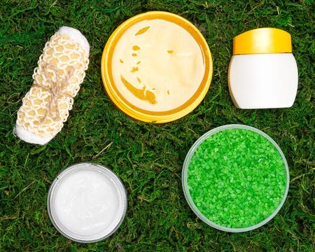 mimos: Spa y de cuidado del cuerpo productos. Primer plano de lavador de cuerpo, abrir frascos llenos de sal gruesa de mar, exfoliante corporal natural y crema de cuidado de piel en color verde musgo. cosm�ticos org�nicos seguros