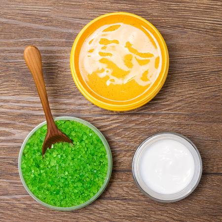 mimos: balneario natural y productos de cuidado del cuerpo. Primer plano de sal marina gruesa, exfoliación corporal y crema de cuidado de la piel en la superficie de madera, vista desde arriba. cosméticos orgánicos seguros