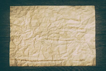 deckle: Close-up of old crumpled paper sheet on wooden surface. Retro style processing