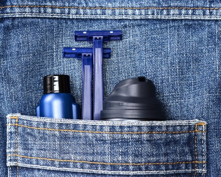 basic care: Mens cosmetics. Shaving foam, disposable razors and aftershave lotion in jeans pocket. Basic skin care cosmetic products and accessories for men. Toiletry and cosmetic travel kit