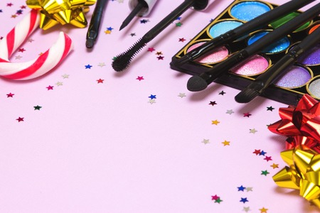 paletas de caramelo: maquillaje de fiesta de Navidad. Brillante del brillo del color de sombra de ojos, rimel, delineador de ojos, brillo de labios, aplicador, cepillos con el bastón de caramelo, arcos de papel de regalo y confeti. Poca profundidad de campo. espacio de la copia Foto de archivo