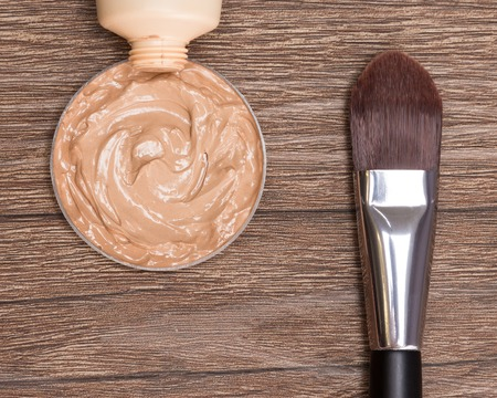 flaws: Close-up of flat makeup brush with liquid foundation squeezed out of tube on dark wooden surface