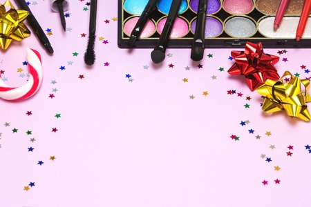 grooming product: Christmas party makeup. Bright color glitter eyeshadow, mascara, eyeliner, lip gloss, lip liners, applicator, brushes with candy cane, gift wrap bows and confetti. Shallow depth of field. Copy space