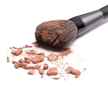Close-up of makeup brush with crushed bronzing powder on white background. Bronzer to face contouring or creating tanned look. Shallow depth of field Stock Photo