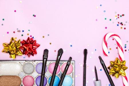 paletas de caramelo: Maquillaje para la fiesta. Brillante del brillo del color de sombra de ojos, rimel, delineador de ojos, brillo de labios de color rojo, conforman cepillos y aplicador con el bastón de caramelo, arcos papel de regalo y confeti sobre fondo de color rosa. espacio de la copia