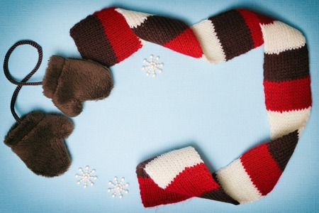 Composition of little fur mittens, knitted scarf and small snowflakes on blue textured background. Cute winter frame with blank space for text