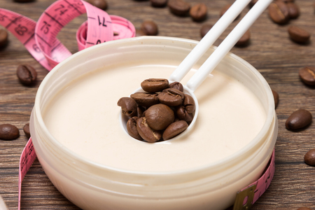 busting: Cellulite busting product. Anti-cellulite cosmetics with caffeine. Jar of cream with coffee essential oil, spoon of coffee beans, body measuring tape on wooden surface. Closeup, shallow depth of field Stock Photo