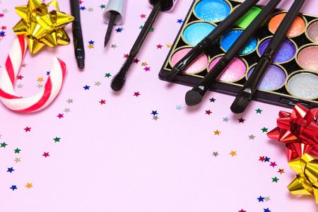 paletas de caramelo: Maquillaje para la fiesta festivo. Brillante del brillo del color de sombra de ojos, rimel, delineador de ojos líquido, brillo de labios, aplicador, cepillos con el bastón de caramelo, arcos de papel de regalo y confeti. Poca profundidad de campo. espacio de la copia Foto de archivo