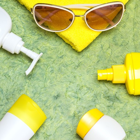 Various cosmetic sunscreen products for face and body skin care, towel and sunglasses. Lotion, milk, spray and cream. Cosmetics containing sun protection factor