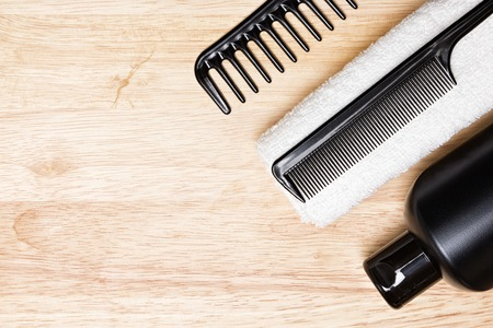 Hair care and styling background. Black bottle, wide tooth and fine tooth combs with white terry cloth towel on wooden surface. Copy space