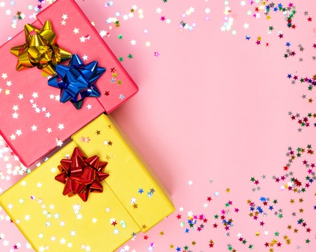 Holiday background with two color gift boxes, wrap bows and sparkling confetti. Copy space Stock Photo