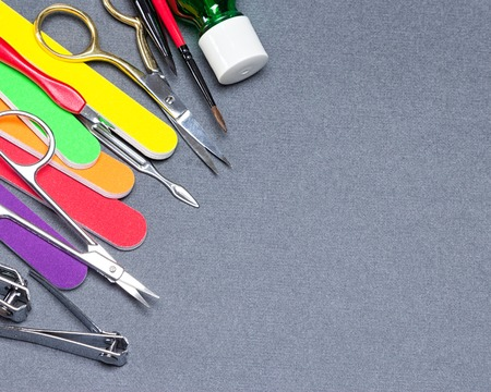 Manicure tools on gray textured surface. Copy space