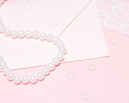 felicitation: Wedding invitation. Envelope, pearl chaplet, small hearts of beads on pink surface with white lace