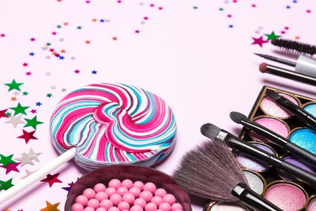 Holiday party makeup cosmetics. Color glitter eyeshadow, blush, liquid eyeliner, mascara, brushes with lollipop and confetti. Shallow depth of field, copy space