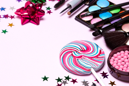 Decorative cosmetics for holiday party make up. Blush, color glitter eyeshadow, liquid eyeliner, mascara, brushes with lollipop, confetti and gift wrap bows. Selective focus, copy space