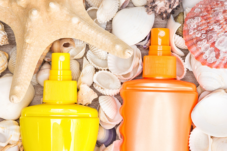 Summer beauty products. Sunscreen sprays with shells and starfish. Must have cosmetics for beach vacation