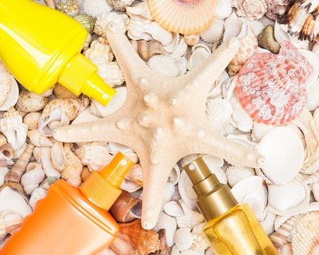 Cosmetic sunscreen products laid out around starfish on various shells. Must have summer beauty products Stock Photo
