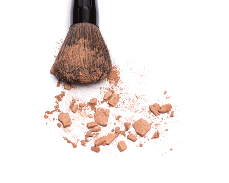 Close-up of makeup brush with crushed bronzing powder on white background. Bronzer for face contouring or creating tanned look