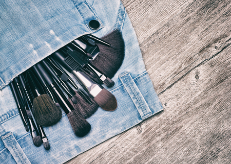 stuff: Professional tools of makeup artist in blue jeans pocket on shabby wooden surface. Make up brushes and applicators. Toned image with copy space Stock Photo