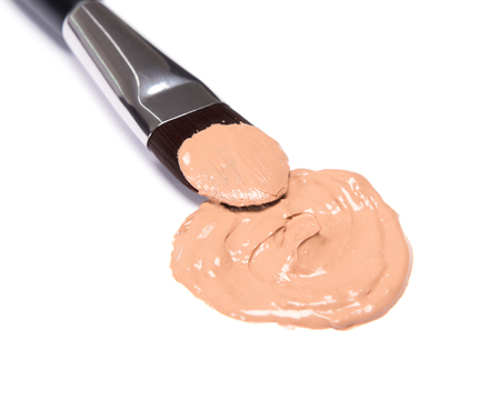 Close-up of flat makeup brush with spot of liquid foundation on white background. Shallow depth of field