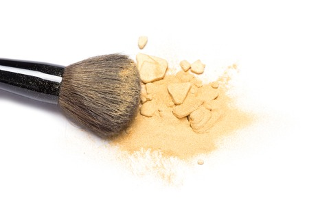 grooming product: Close-up of makeup brush with crushed mineral shimmer powder golden color on white background Stock Photo
