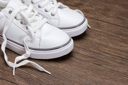 shoestrings: White sneakers on dark wooden surface. Shoes for women in sport fashion style. Copy space Stock Photo