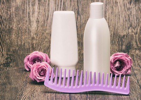 Hair care and styling cosmetics for women. Hair beauty products and wide tooth comb with roses on wooden surface. Toned image with copy space
