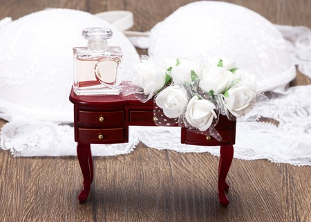 Close-up of perfume with white flowers on small chest of drawers on the background of white lace lingerie. Bride s accessories. Wedding preparations
