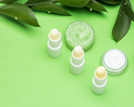Lip balms, cream, gentle honey scrub with green leaves. Selective focus, copy space