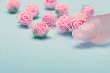 Perfume spray bottle with pink roses on blue textured background. Side view, very shallow depth of field. Vintage toning, copy space