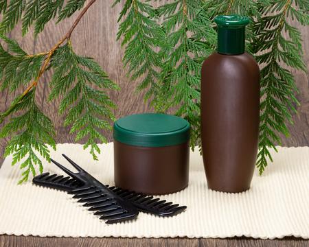 Shampooing, masque capillaire et peignes sur fond de branches de plantes vertes fraîches. Cosmétiques naturels de soins capillaires