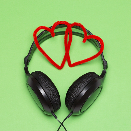 Music for people in love concept. Headphones with red hearts on green background Stock Photo