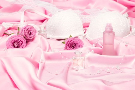 Perfumes with roses and women underwear on pink silk. Choice of fragrance for romantic date concept