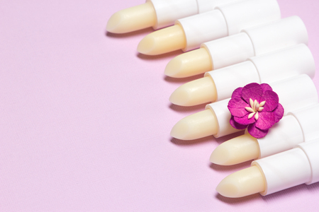Lip balms with small paper flower on lilac background, copy space Imagens