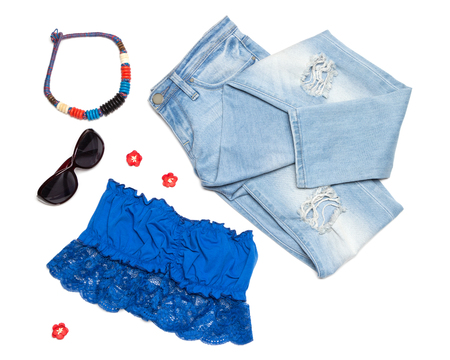 Fashion summer women outfit. Ripped skinny jeans, bandeau top, necklace and sunglasses on white background Stock Photo