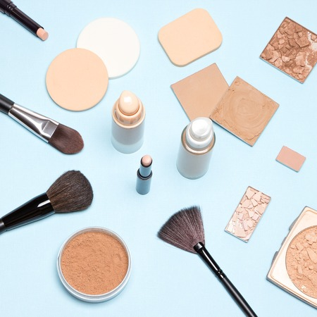 Makeup products to even out skin tone and complexion: concealer, foundation, cosmetic powder. Top view