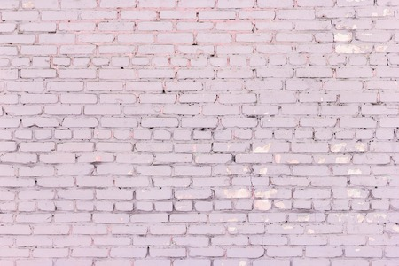 Painted dirty pink brick wall. Old shabby brickwork dusty rose color Stock Photo