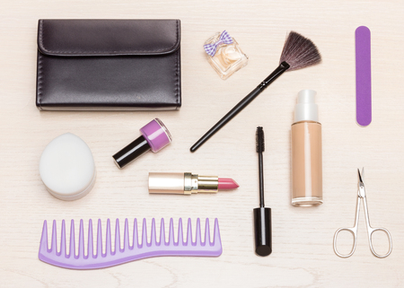 Basic contents of cosmetic bag on light wood table, flat lay. Essential make up beauty products and women accessories