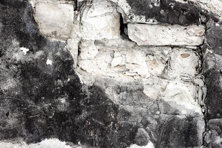 Fragment of brick wall with fallen off plaster. Crumbled old shabby brickwork texture. White bricks, black coating. Grunge background Standard-Bild