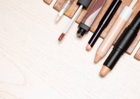 Different types of make-up concealers on white wooden table. Diagonal arrangement, top view, copy space