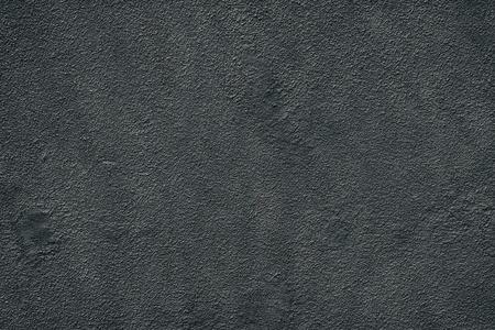 Black fine textured old cement plaster. Dark dappled wall background Stock Photo