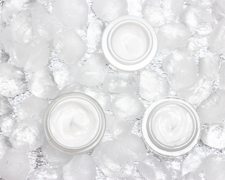 Cooling effect face skincare products. Glass jars of moisturizing cream surrounded by ice cubes. Top view, close-up